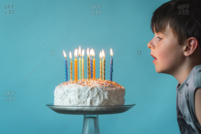 Boy ready to blow out candles on birthday cake against blue backdrop.