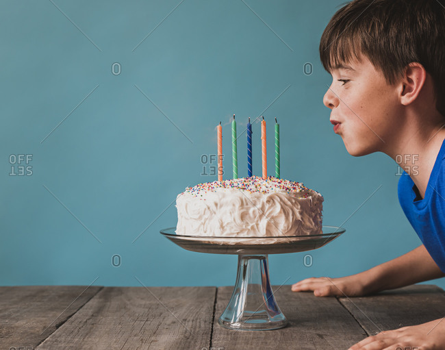 Boy blowing out candles on a birthday cake against blue background.