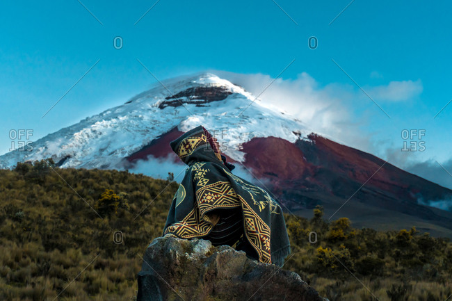 Ecuador, Cotopaxi Province - May 8, 2019: Person watching a volcano with snow on the summit, Cotopaxi