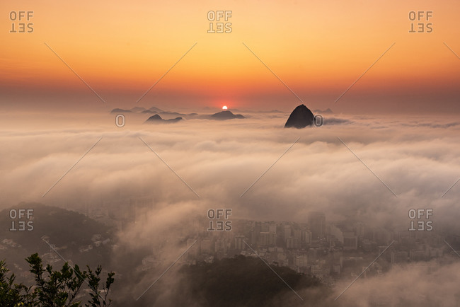 Beautiful landscape of sunrise and mountain rising above low clouds