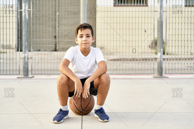Kid playing basketball alone in a street court
