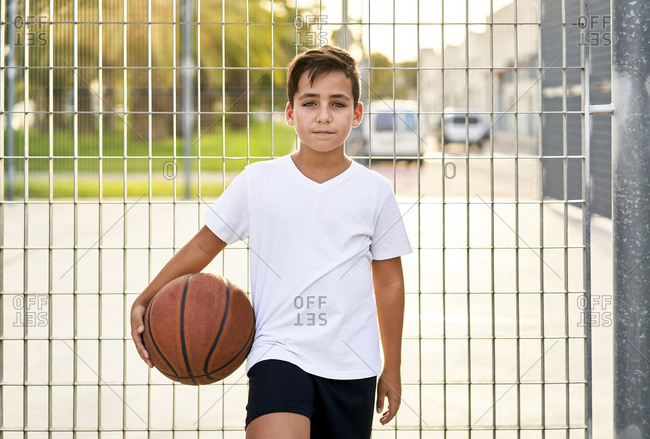 Kid with Green eyed playing basketball alone in a street court