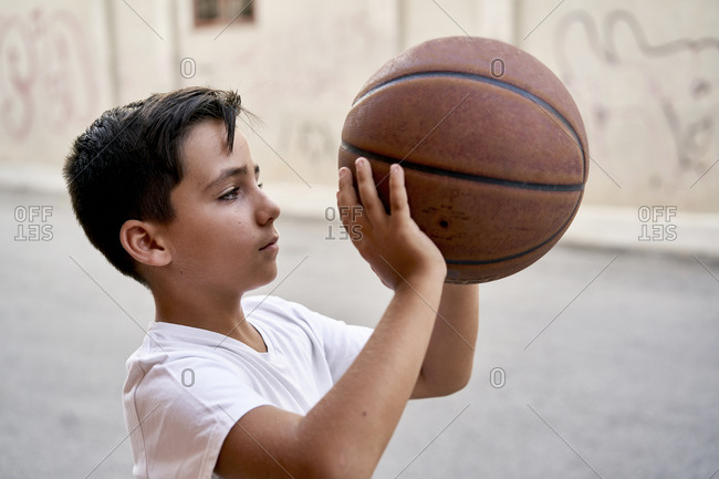 Kid playing basketball alone in the street