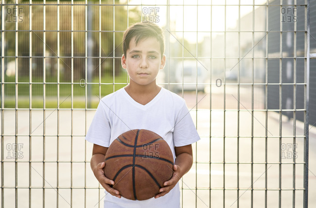 Kid with Green eyed playing basketball alone in a street
