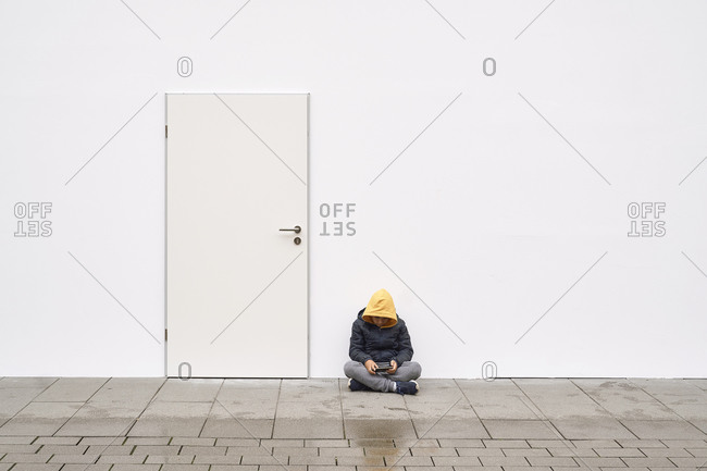 Kid using his mobile in the street with a white wall background