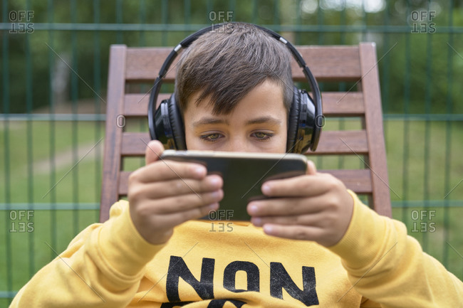 Kid listen music in his mobile with headphones