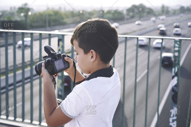 Child photographer with white hat taking photos with his camera