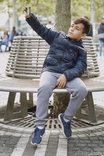 Young boy taking a photo with his telephone on a bench in the city.