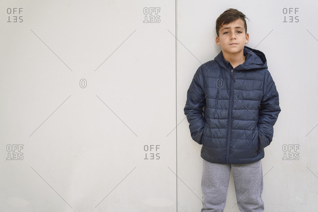 Green eyed kid with blue jacket posing in a white wall