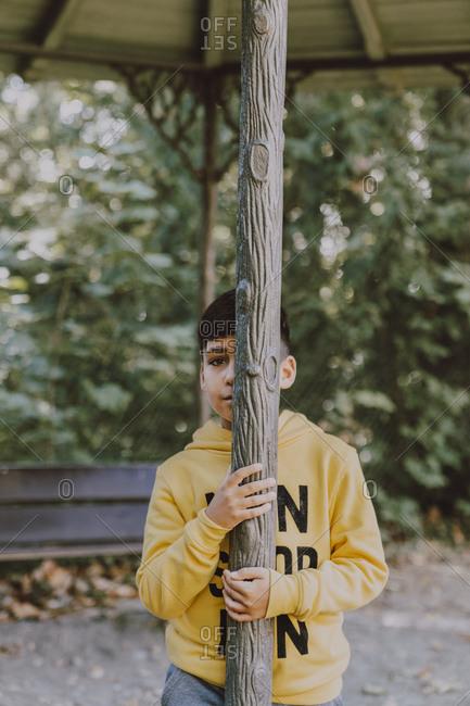 Green eyed kid hidden in a tree trunk portrait
