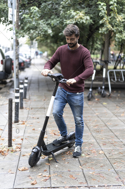 Bearded man riding by electric scooter in the street