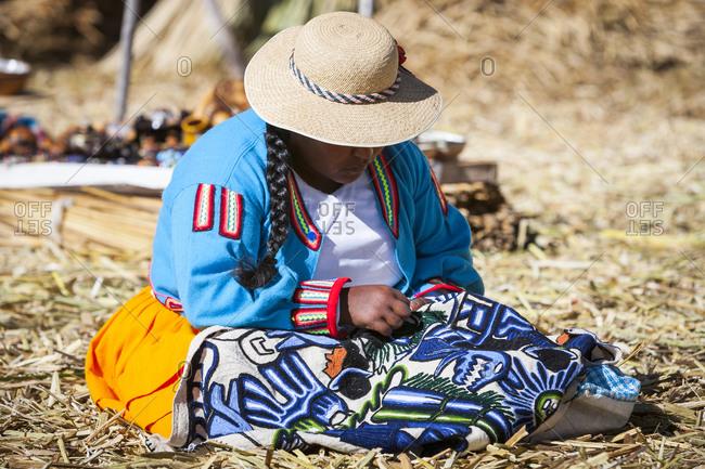 Peru, Puno - August 5, 2008: Native woman sewing on floating islands of Uros, Lake Titicaca, Peru.