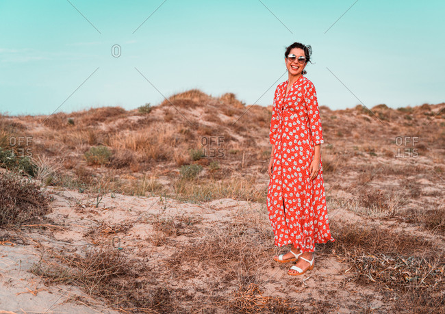 Beautiful woman in red dress into the white sand dunes at sunset in a Mediterranean beach