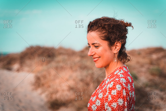 Beautiful woman in red dress into the white sand dunes at sunset