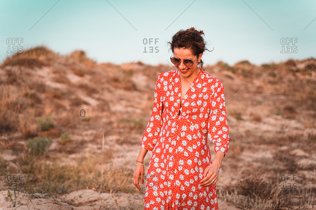 Curly brunette in red dress into the white sand dunes at sunset
