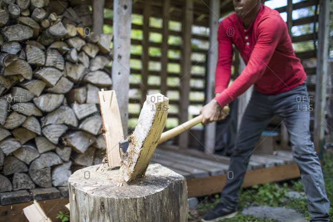 Strong Indian man splitting firewood with sharp axe.