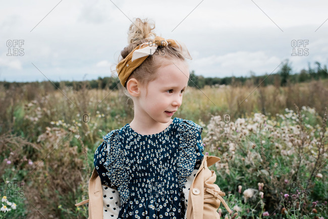 Portrait of a pretty young girl stood in a field of wild flowers