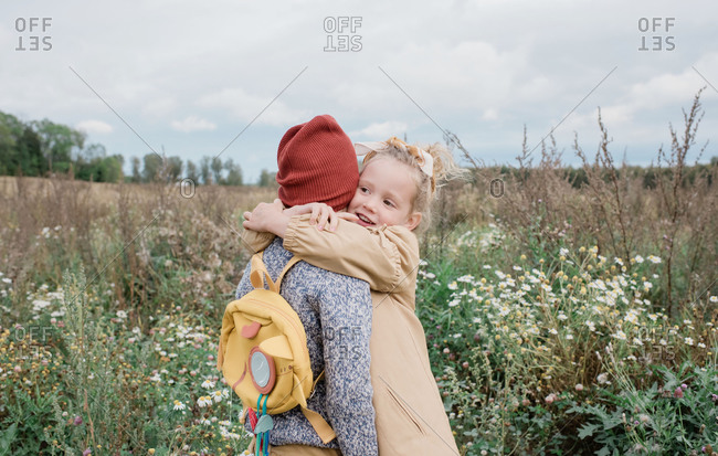 Sister hugging her brother stood in a field of wild flowers in fall