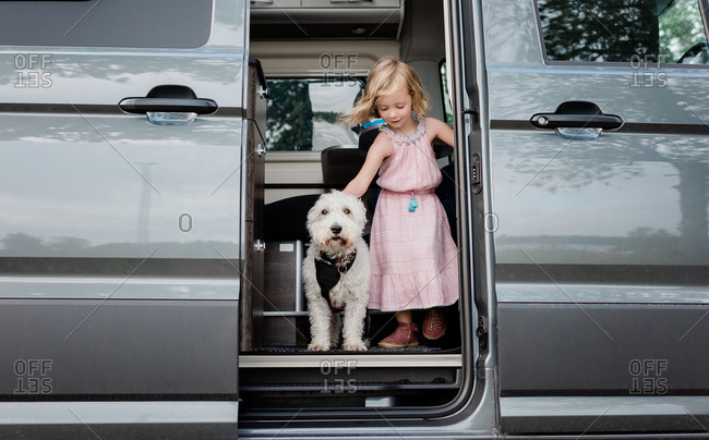 Portrait of a young girl camping in a camper van with her dog