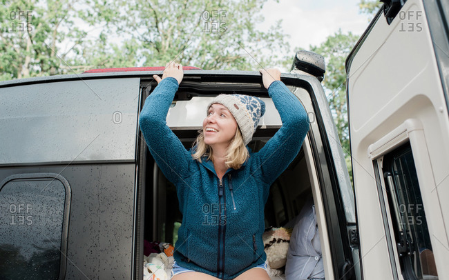 Woman looking out of a camper van in the rain whilst camping