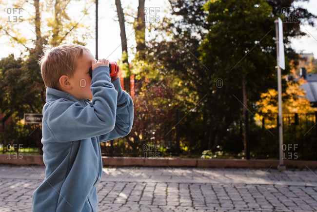 Young boy stood in a street looking through binoculars