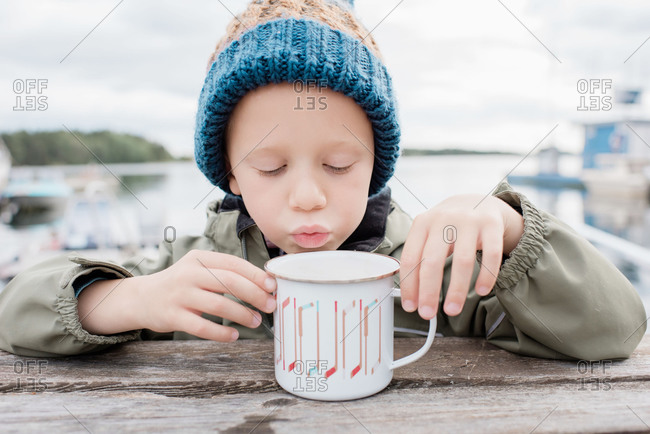 Young boy drinking hot chocolate outside on a picnic bench in winter