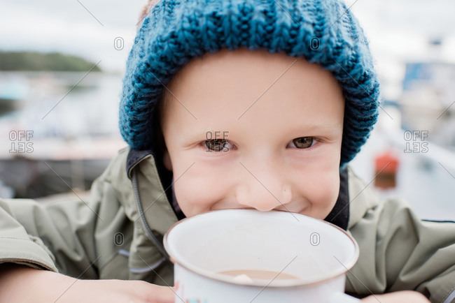Close up portrait of a young boy drinking hot chocolate outside