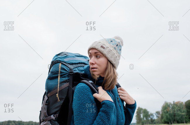 Woman looking behind her whilst backpacking on an adventure
