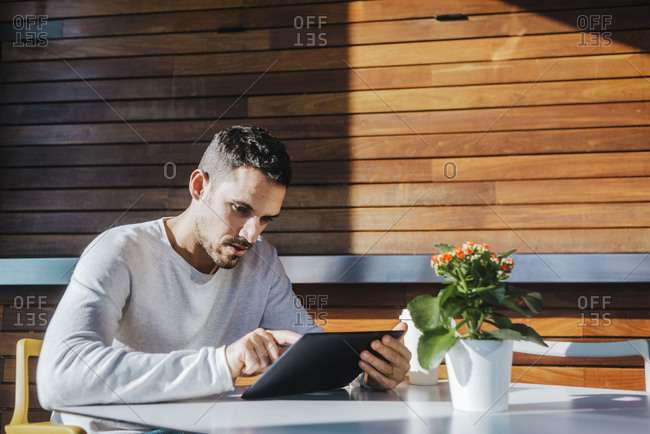 Stylish young man sitting on couch in a cafe using tablet