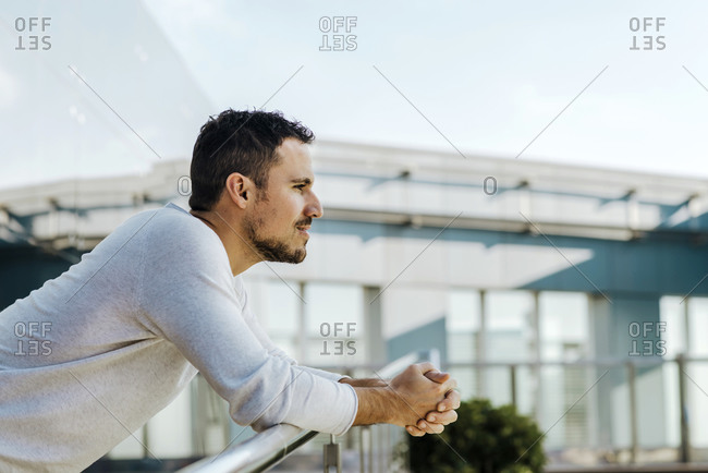 Man leaning on railing of footbridge looking at distance