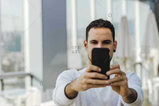 Young man taking a selfie with smartphone