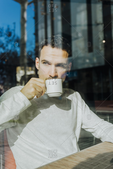 Man drinking coffee while looking away in a cafe shop