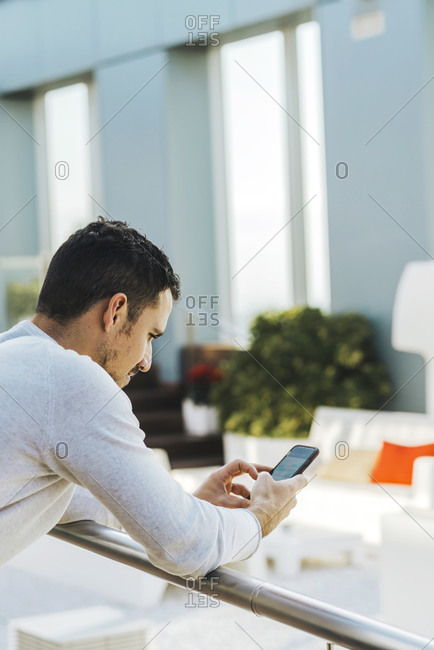 Young man leaning on railing while using mobile phone