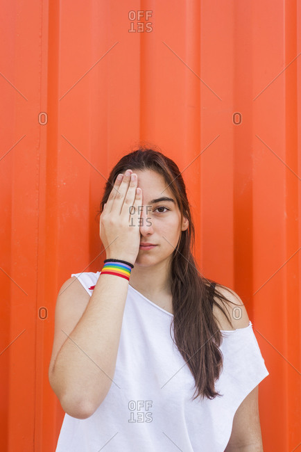 Woman with long dark hair covering her eye while looking camera