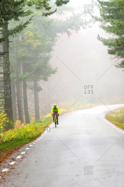 Healthy man riding a bicycle on a mountain road in a foggy day