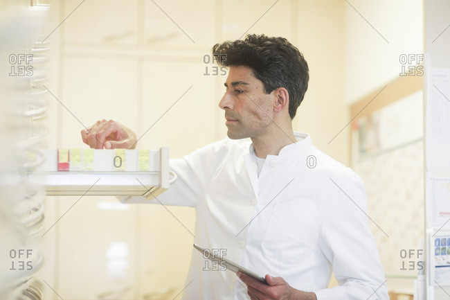 Pharmacist in a pharmacy with a tablet