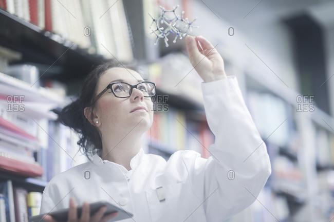Young scientist female with model in a library