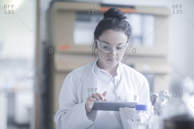Young scientist female with tablet in an office