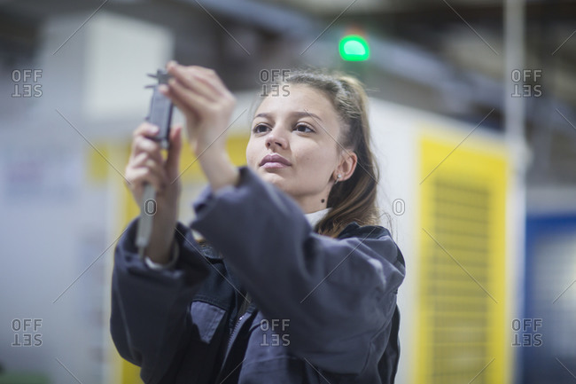 Industrial plant with an engineer female controlling a tool