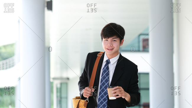 Smiling young businessman holding coffee cup while coffee break.