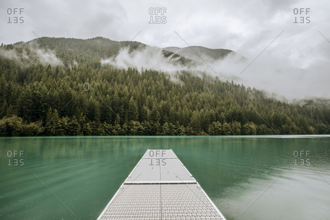 A dock on a glacial lake surrounded by misty mountains and forest