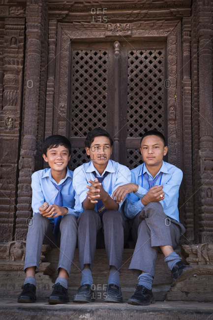 Nepal, Central Development Region, Kathmandu - October 23, 2013: Students in school uniforms sit outside a temple in Kathmandu, Nepal.