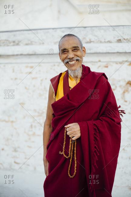 Nepal, Central Development Region, Kathmandu - November 14, 2013: A monk smiles at Boudhanath Stupa in Kathmandu, Nepal.