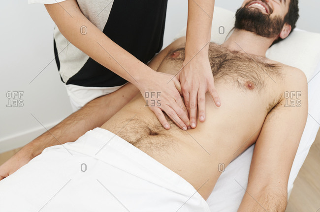 Closeup of a physiotherapist applying pressure to the abdomen of a male patient lying on an examination table in her office