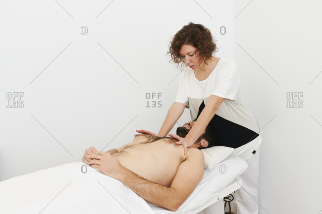 Physiotherapist treating the chest and shoulders of a male patient lying on an examination table in her office