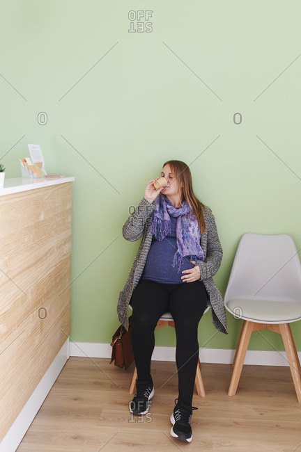Young pregnant woman drinking water while waiting for an appointment in the reception area of a doctor's office
