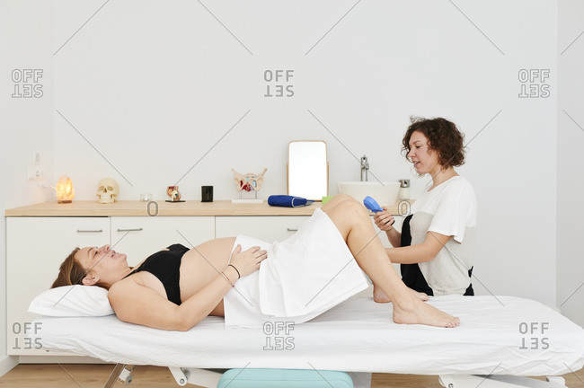 Physiotherapist using equipment to test the pelvic floor muscle strength of a pregnant patient lying on a table in her office