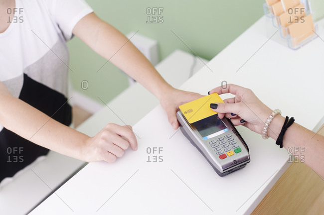 Cropped closeup of a woman standing at a reception desk using a credit card and terminal to pay for her doctor's appointment