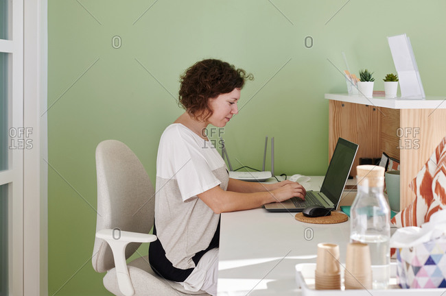 Medical assistant sitting at her desk at the reception counter of a doctor's office working on a laptop