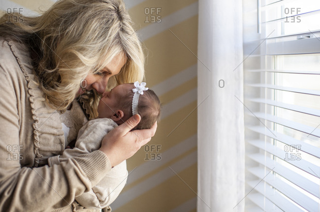 Mother happily holding newborn daughter up to face at home